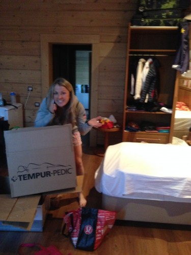 Holly on the phone with her husband while getting a tempur-pedic cover set up on the bed!