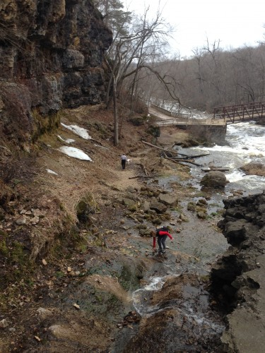 My family climbing around the side of the falls at Willow River State Park