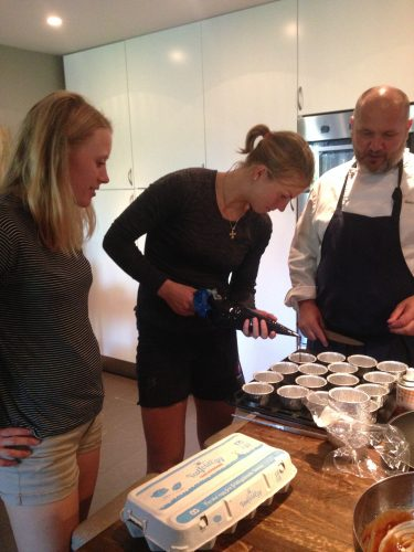 The team chef teaches Astrid how to use the piping bag.